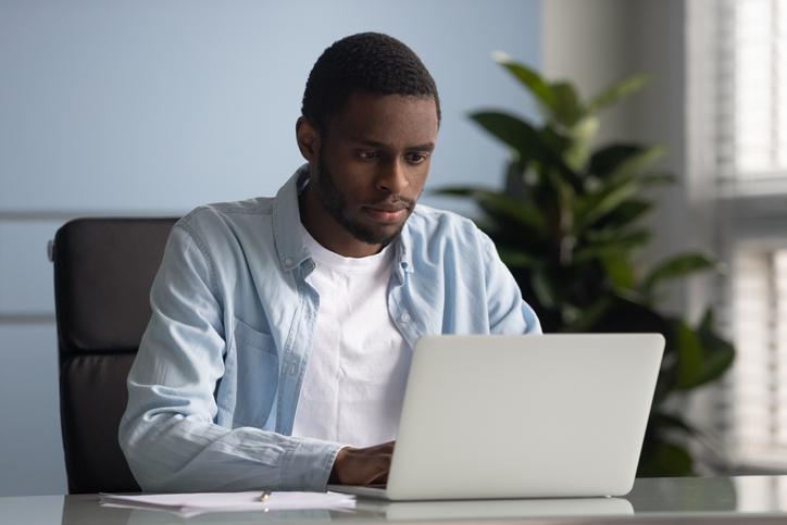 African American male employee working on laptop in office
